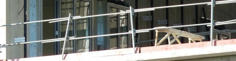 Installation des portes-fenêtres du bâtiment B, donnant sur la faille avec le bâtiment C